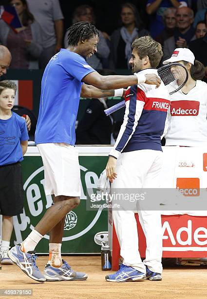 Gael Monfils of France celebrates with Captain Arnaud Clement of France after defeating Roger Federer of Switzerland during day one of the Davis Cup...