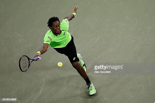 Gael Monfils of France returns a shot against Roger Federer of Switzerland during their men's singles quarterfinal match on Day Eleven of the 2014 US...