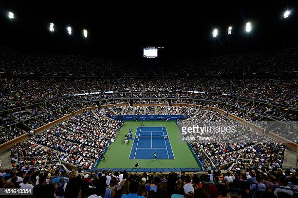 Gael Monfils of France serves to Roger Federer of Switzerland during their men's singles quarterfinal match on Day Eleven of the 2014 US Open at the...