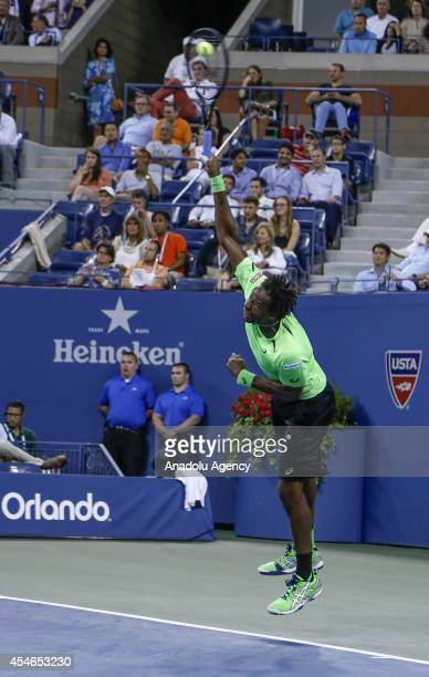 Gael Monfils of France serves to Roger Federer of Switzerland during their men's singles quarterfinal tennis match on Day 11 of the 2014 US Open at...