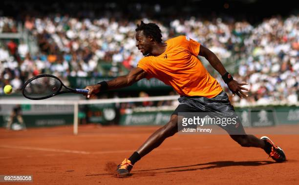 Gael Monfils of France stretches to play a backhand during mens singles fourth round match against Stan Wawrinka of Switzerland on day nine of the...