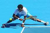 Gael Monfils of France stretches to play a forehand during his match against Lleyton Hewitt of Australia during day four of the AAMI Classic at...