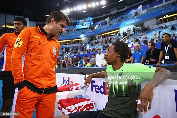 Gael Monfils of the Indian Aces discusses his injury with team coach Fabrice Santoro after his match against Novak Djokovic of the UAE Royals during...