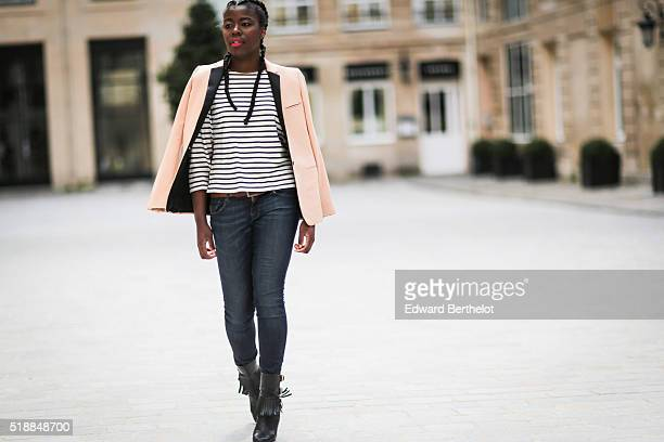 Gaelle Dago is wearing a Saint James striped tshirt a Celine salmon colored blazer jacket April 77 blue jeans and black boots during a street style...