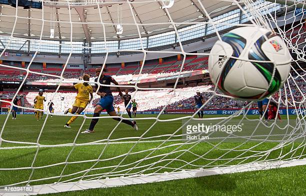 Gaelle Enganamouit of Cameroon scores her second goal of the game as Katherine Ortiz of Ecuador looks on during the FIFA Women's World Cup Canada...