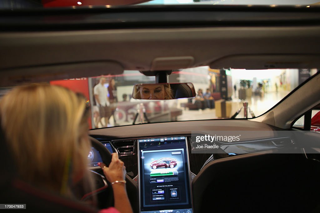 Gaelle Freer looks at a Tesla motor company car in a dealership at the Dadeland Mall on June 6, 2013 in Miami, Florida. The electric car maker is trying to make a move by selling their cars, that can cost between $62,400 and $82,400, into malls and stores.