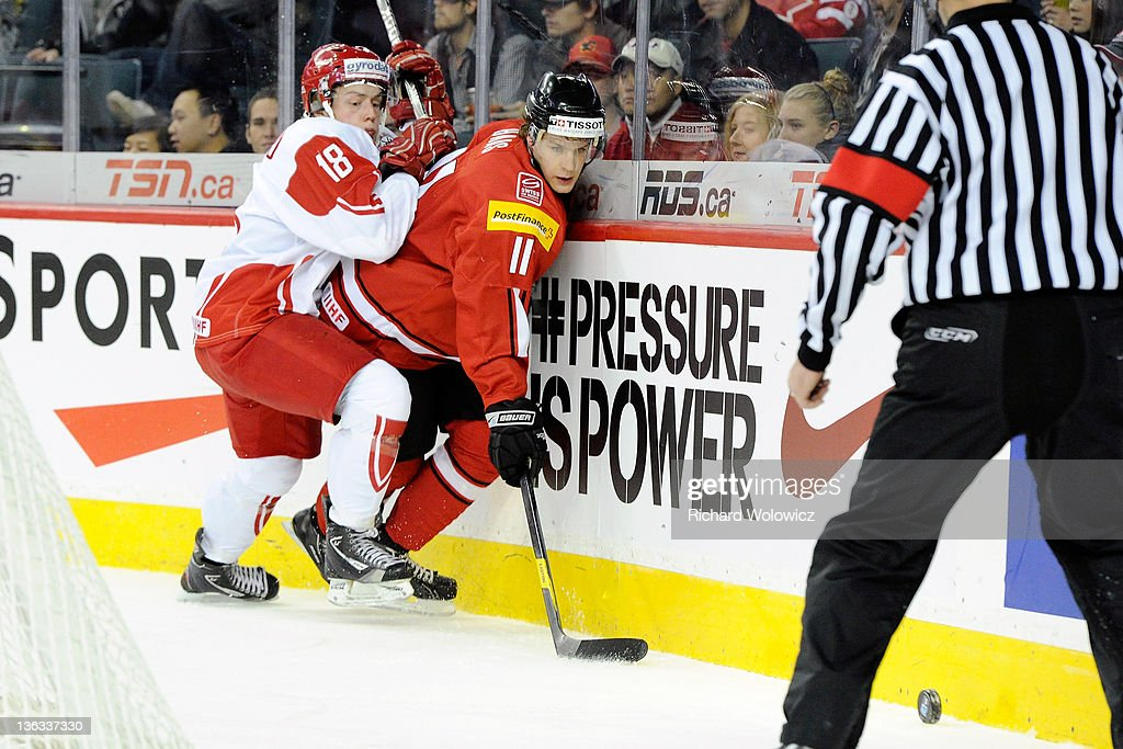Gaetan Haas #11 of Team Switzerland and Thomas Christensen #18 of Team Denmark battle for the puck during a relegation game at the 2012 World Junior Hockey Championships at the Saddledome on January 2, 2012 in Calgary, Alberta, Canada.