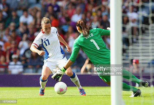 Gaetane Thiney of France looks for a way around USA goalkeeper Hope Solo during the Women's Football first round Group G Match of the London 2012...