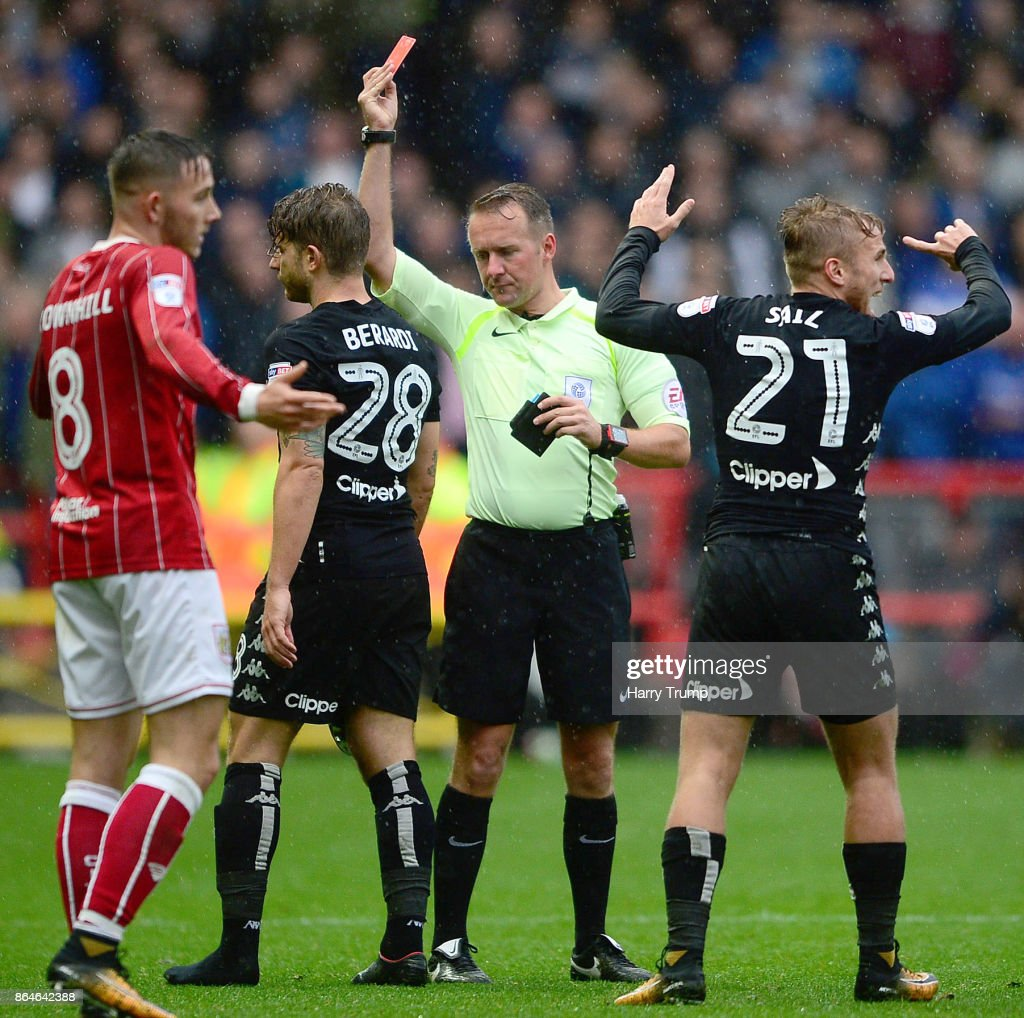 Gaetano Berardi of Leeds United (2L) is shown a red card during the Sky Bet Championship match between Bristol City and Leeds United at Ashton Gate on October 21, 2017 in Bristol, England.