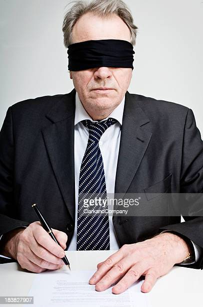 Gagged and Blindfolded Businessman Signing A Contract