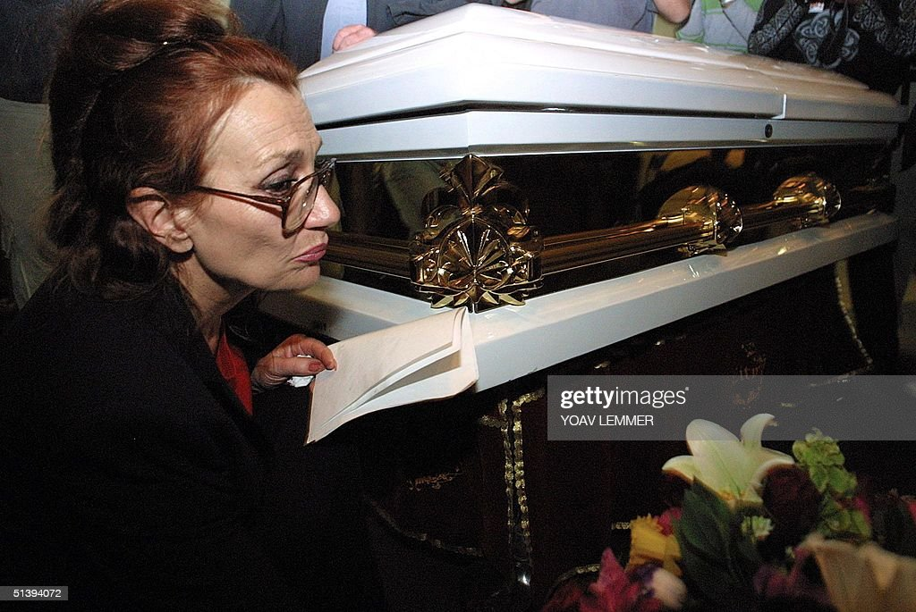 Gail Johnson, the foster mother of Nkosi Johnson spends a private moment next to her sons coffin during his funeral service at a Johannesburg church 09 June 2001. Nkosi was the longest surviving child with AIDS in South Africa, died 01 June 2001 at the age of 12, and was burried at the Westpark cemetery in Johannesburg