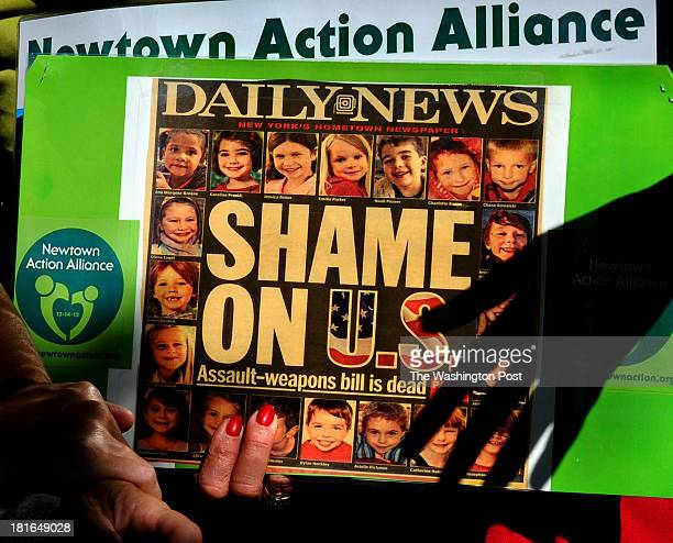 Gail Lehmann of the Newtown Action Alliance holds a reproduction of the newspaper headline reporting the failure of gun control measures that were...
