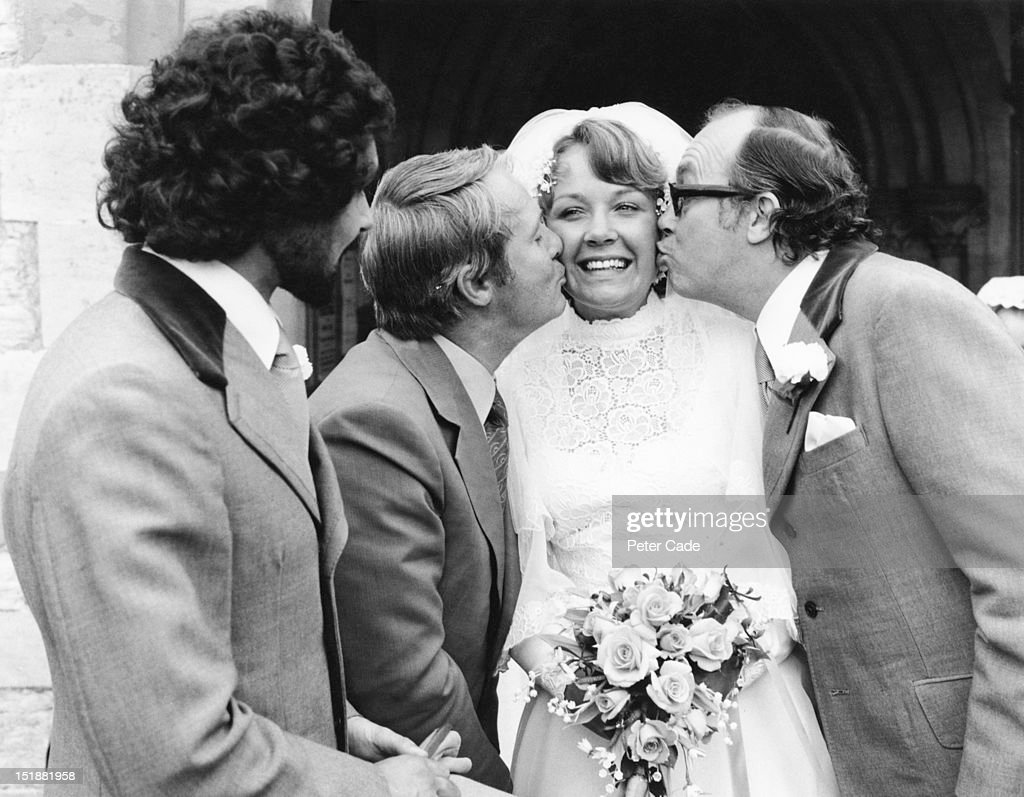 Gail Morecambe recieves a kiss from her father, comedian <a gi-track='captionPersonalityLinkClicked' href=/galleries/search?phrase=Eric+Morecambe&family=editorial&specificpeople=215236 ng-click='$event.stopPropagation()'>Eric Morecambe</a> (1926 - 1984, right) and his showbusiness partner <a gi-track='captionPersonalityLinkClicked' href=/galleries/search?phrase=Ernie+Wise&family=editorial&specificpeople=211147 ng-click='$event.stopPropagation()'>Ernie Wise</a> (1925 - 1999) at her wedding at St Nicholas Church, Harpenden, Hertfordshire, 6th September 1975. On the left is the groom, Paul Jarvis.