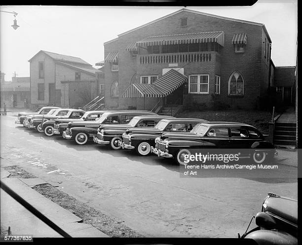 Gaines Funeral Home with striped awnings and nine cars including hearse parked outside in lot Auburn Street East Liberty Pittsburgh Pennsylvania...