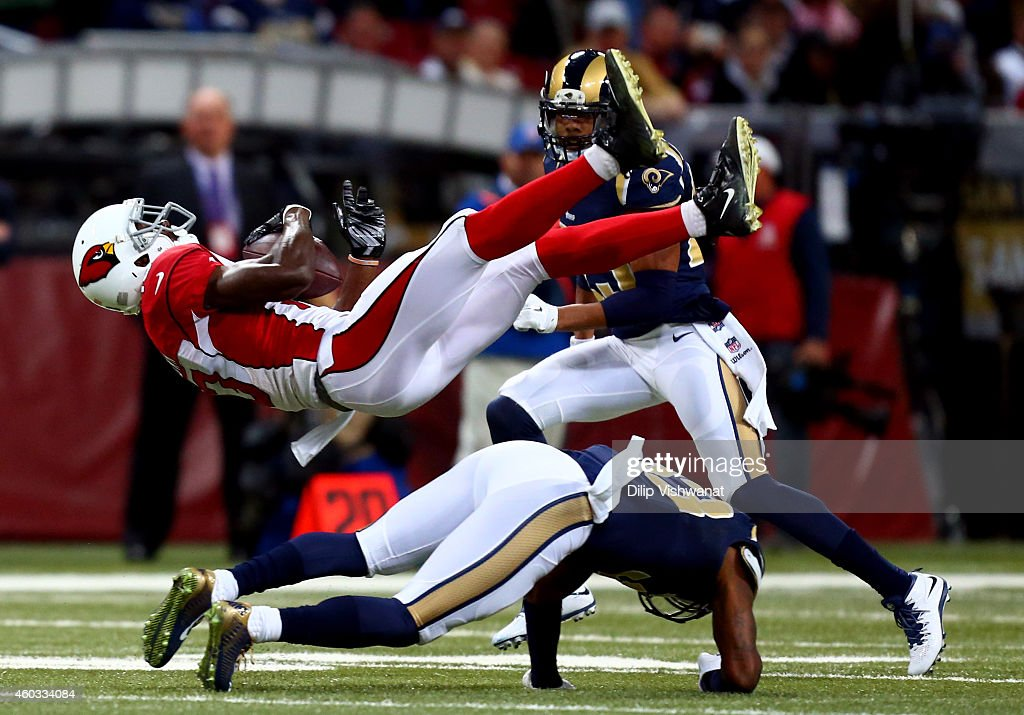 E.J. Gaines #33 of the St. Louis Rams tackles Jaron Brown #13 of the Arizona Cardinals after a reception thrown by Drew Stanton #5 in the first quarter during their game at Edward Jones Dome on December 11, 2014 in St Louis, Missouri.