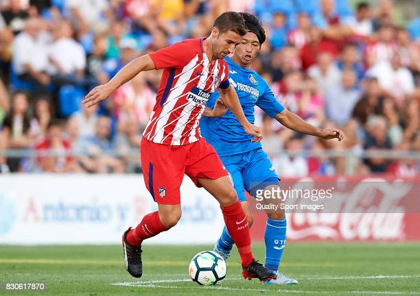 Gaku Shibasaki of Getafe is challenged by Gabi of Atletico de Madrid during the Pre Season Friendly match between Getafe CF and Atletico de Madrid at...