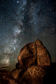 The Milky Way galaxy rises behind a rock covered with Native American petroglyphs, near Gila Bend, Arizona.