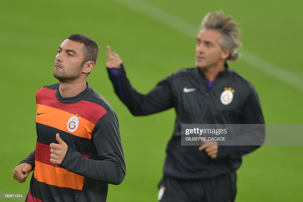 Galatasaray forward Burak Yilmaz (L) and new coach Roberto Mancini attend a training session on the eve of the Champion's League football match Juventus vs Galatasaray on October 1, 2013 in Turin. Mancini, sacked by Manchester City at the end of last season following a shock defeat to Wigan in the final of the FA Cup, signed a three-year contract to manage the struggling Turkish champions. AFP PHOTO / GIUSEPPE CACACE