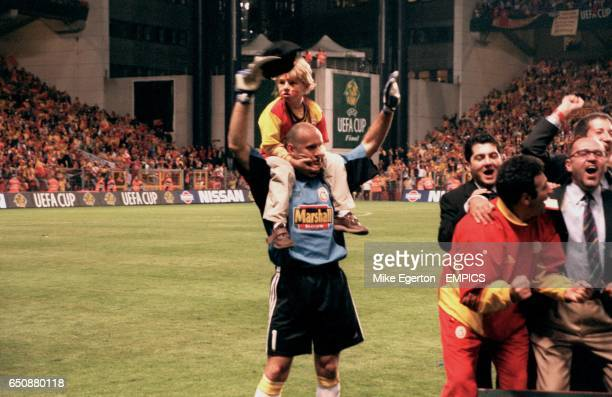 Galatasaray goalkeeper Claudio Taffarel celebrates winning the UEFA Cup with his son