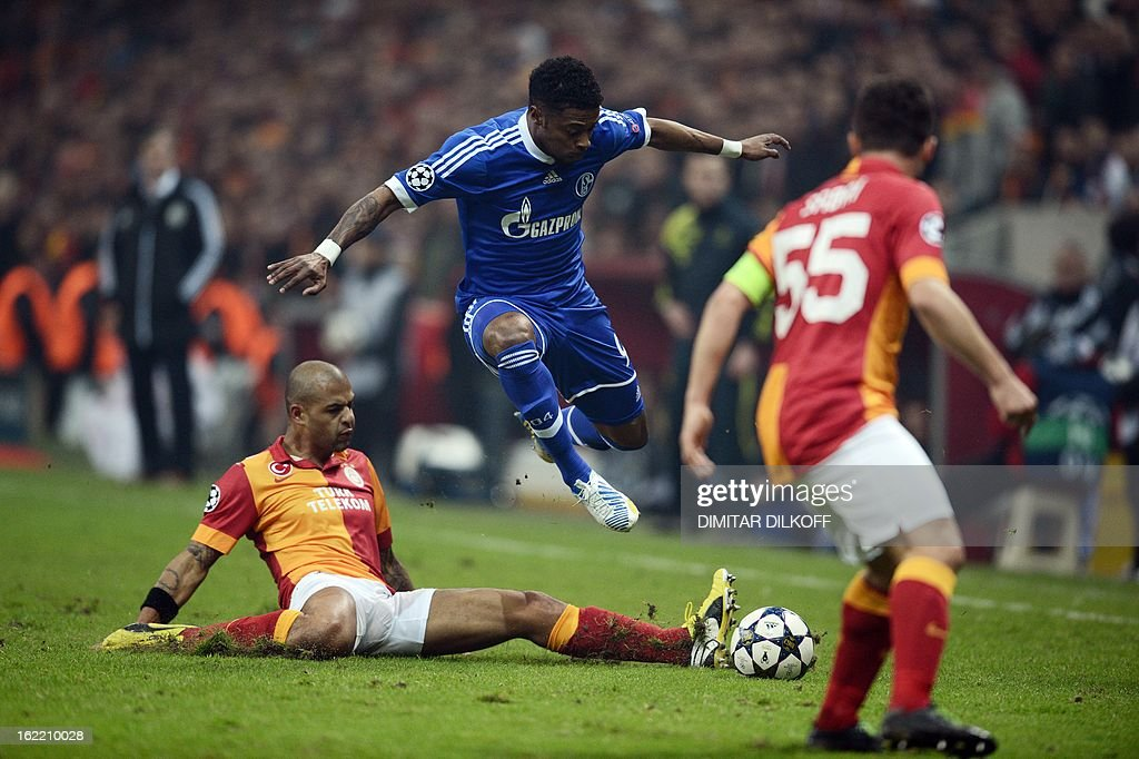 Galatasaray midfielder Felipe Melo (L) tackles FC Schalke 04 midfielder Michel Bastos (C) during the UEFA Champions League football match Galatasaray vs FC Schalke 04 at the Ali Samiyen stadium in Istanbul on February 20, 2013. AFP PHOTO / DIMITAR DILKOFF