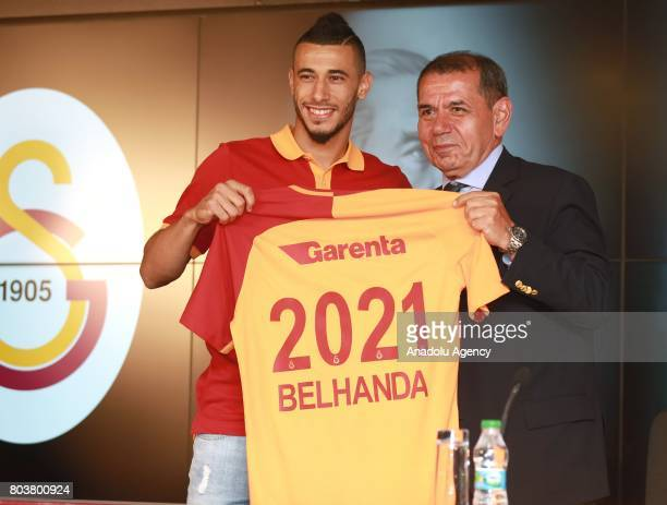 Galatasaray Sports Club President Dursun Ozbek and new signing Younes Belhanda pose with Galatasaray jersey during signing ceremony at Turk Telekom...