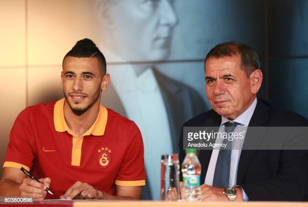 Galatasaray Sports Club President Dursun Ozbek stands next to Galatasaray's new signing Younes Belhanda as he signs for Galatasaray at Turk Telekom...