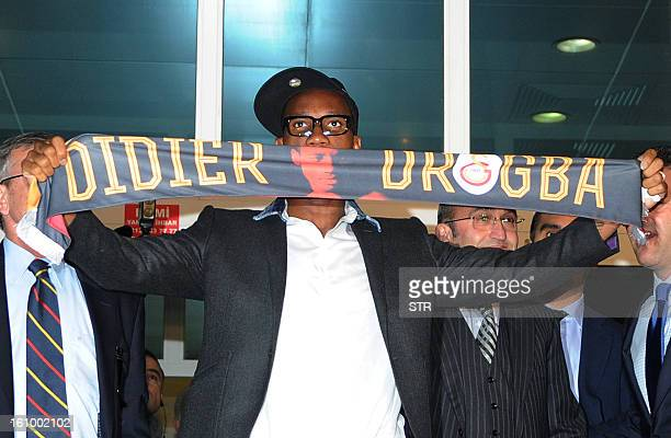 Galatasaray's football club new forward Didier Drogba from Ivory Coast presents his new team scarf as he arrives at the Ataturk airport in Istanbul...