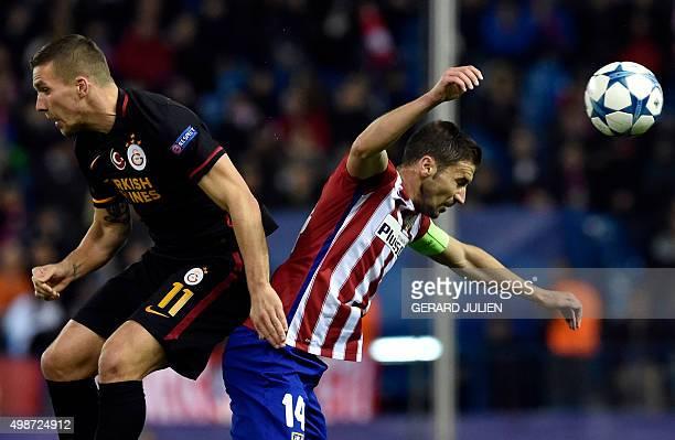 Galatasaray's German forward Lukas Podolski and Atletico Madrid's midfielder Gabi jump for the ball during the UEFA Champions League Group C football...