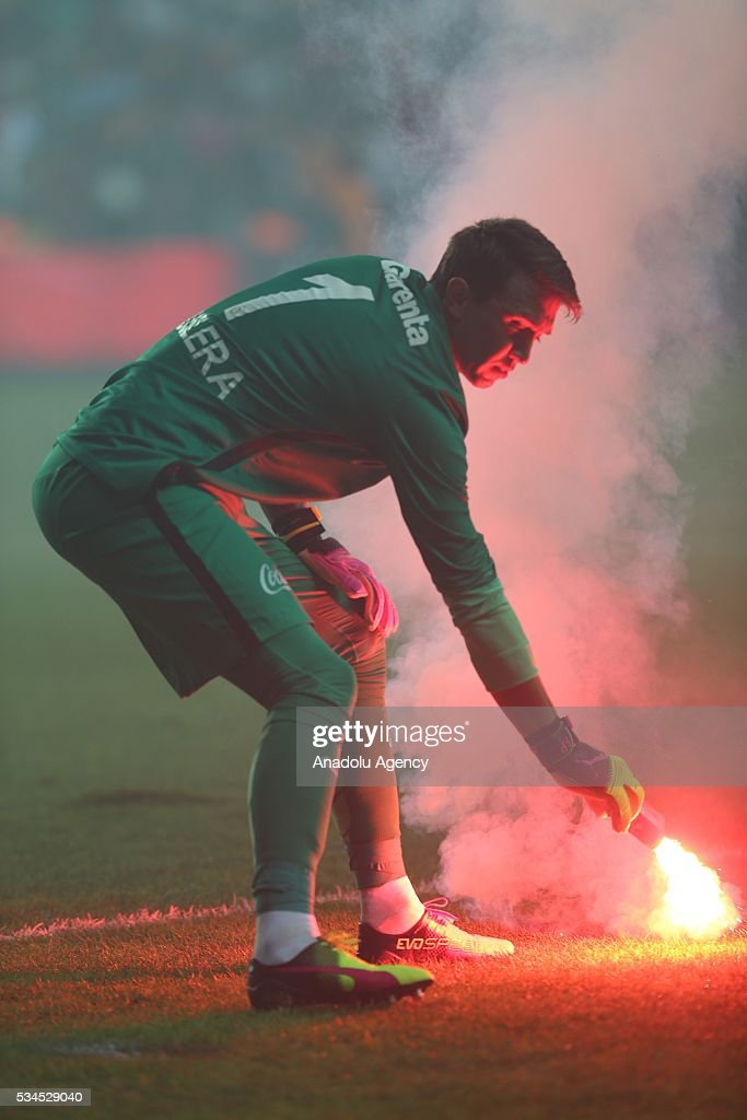 Galatasaray's goalkeeper Fernando Muslera holds a torch thrown by the fans during the Ziraat Turkish Cup Final match between Galatasaray and Fenerbahce at Antalya Ataturk Stadium in Antalya, Turkey on May 26, 2016.