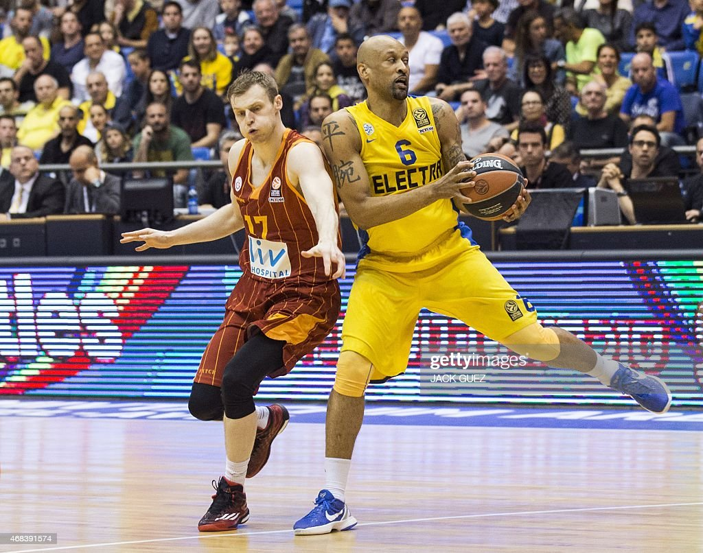 Galatasaray's guard Ender Arslan (L) attempts a steal on Maccabi's guard Devin Smith during the Top 16 Euroleague basketball match between Maccabi Electra Tel Aviv and Galatasaray Liv Hospital on April 2, 2015, at the Nokia stadium in the Mediterranean coastal city of Tel Aviv, Israel.