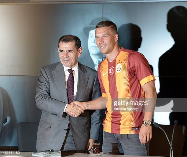 Galatasaray's latest transfer German midfielder Lukas Podolski and the club president Dursun Ozbek shake hands during the signing ceremony for the 3...
