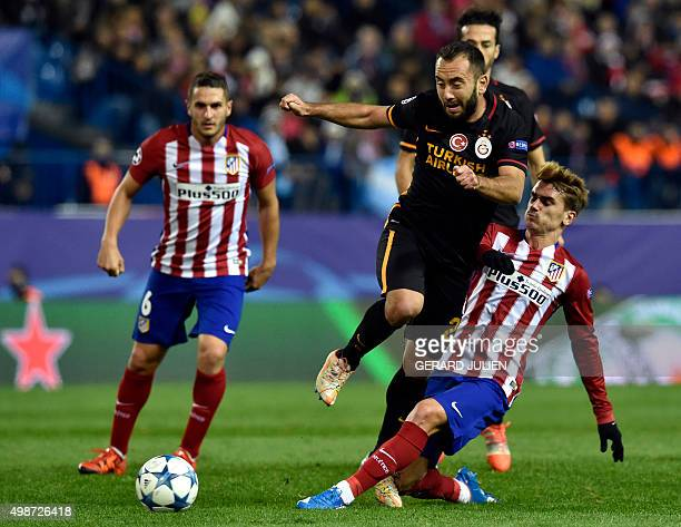 Galatasaray's midfielder Olcan Adin vies with Atletico Madrid's French forward Antoine Griezmann as Atletico Madrid's midfielder Koke looks on during...