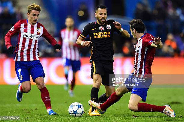 Galatasaray's midfielder Yasin Oztekin vies with Atletico Madrid's Uruguayan defender Diego Godin and Atletico Madrid's French forward Antoine...