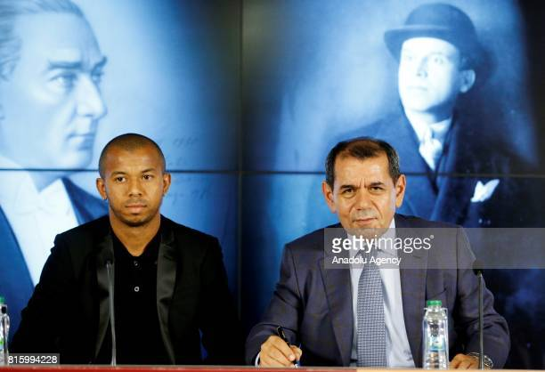 Galatasaray's new transfer Mariano Ferreira Filho signs a contract as Galatasaray's President Dursun Ozbek stand near him during the signing ceremony...