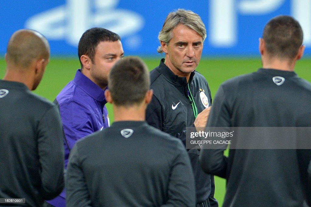 Galatasaray's newly appointed headcoach Roberto Mancini speaks with his players during a training session on the eve of the Champion's League football match Juventus vs Galatasaray on October 1, 2013 in Turin. Mancini, sacked by Manchester City at the end of last season following a shock defeat to Wigan in the final of the FA Cup, signed a three-year contract to manage the struggling Turkish champions. AFP PHOTO / GIUSEPPE CACACE