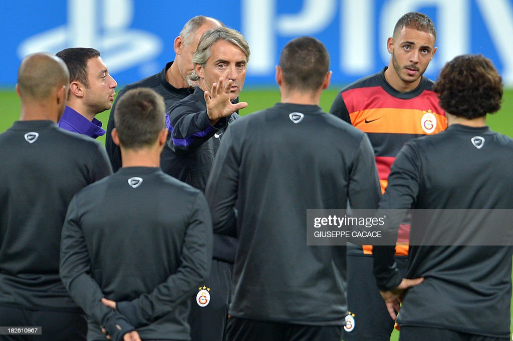 Galatasaray's newly appointed headcoach Roberto Mancini (C) speaks with his players during a training session on the eve of the Champion's League football match Juventus vs Galatasaray on October 1, 2013 in Turin. Mancini, sacked by Manchester City at the end of last season following a shock defeat to Wigan in the final of the FA Cup, signed a three-year contract to manage the struggling Turkish champions.