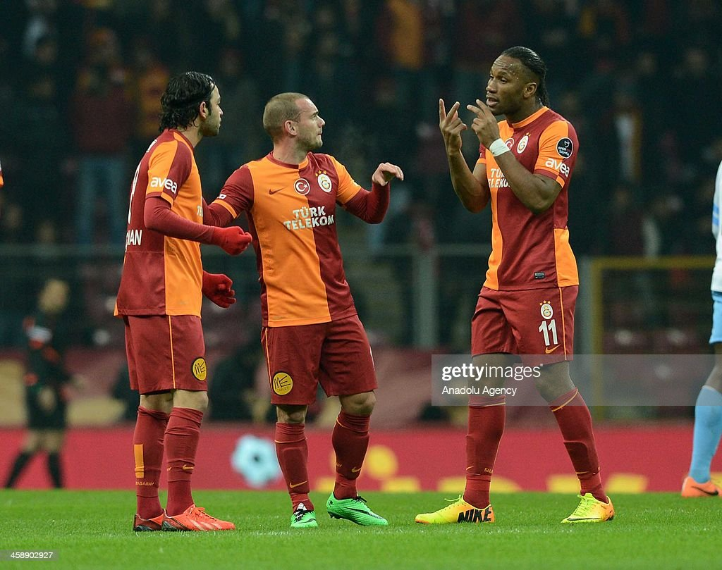 Galatasaray's (L to R) Selcuk Inan, Wesley Sneijder and Didier Drogba talk after a position during the Turkish Spor Toto Super League match between Galatasaray and Trabzonspor at Ali Sami Yen Sports Complex on December 22, 2013 in Istanbul, Turkey.