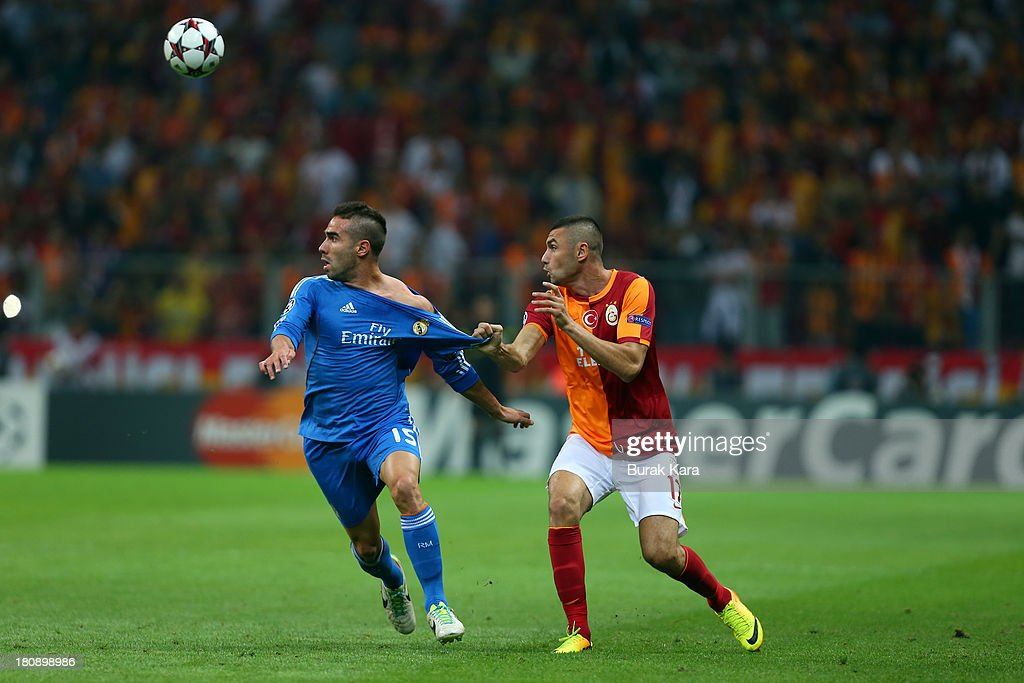 Galatasaray's striker Burak Yilmaz (R) pulls Daniel Carvajal of Real Madrids jersey during UEFA Champions League Group B match at the Ali Sami Yen Area on September 17, 2013 in Istanbul, Turkey.