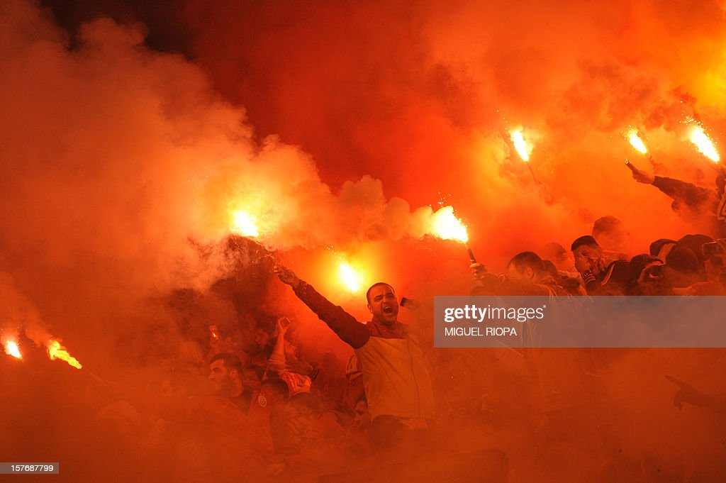 Galatasaray's supporters light flares during the UEFA Champions League Group H football match SC Braga vs Galatasaray at the AXA Stadium in Braga, northern Portugal, on December 5, 2012. Galatasaray won the match 2-1. AFP PHOTO / MIGUEL RIOPA