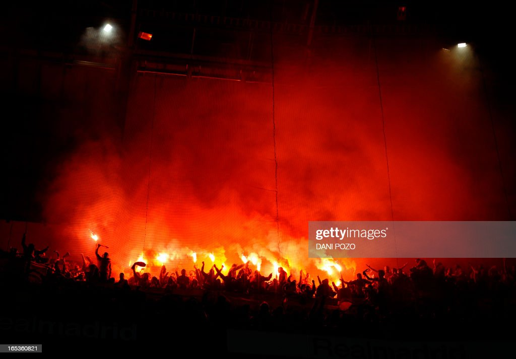 Galatasaray's supporters light flares during the UEFA Champions League quarter-final first leg football match Real Madrid vs Galatasaray on April 3, 2013 at Santiago Bernabeu stadium in Madrid.