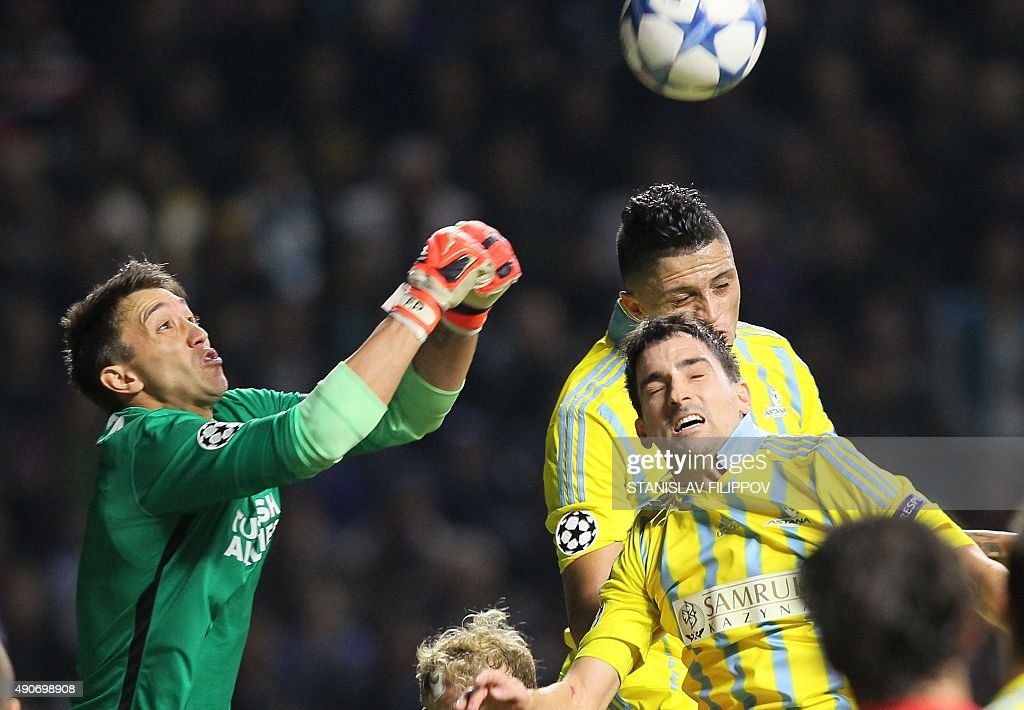 Galatasaray's Uruguayan goalkeeper Fernando Muslera fights for the ball with Astana's defender from BosniaHerzegovina Marin Anicic and Astana's...