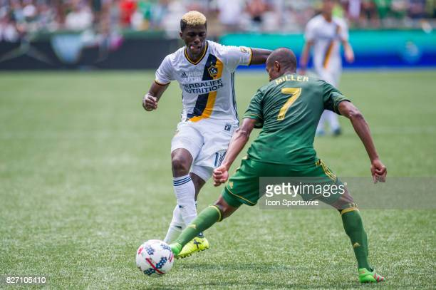 Galaxy forward Gyasi Zardes makes a pass marked by Portland Timbers defender Roy Miller during the final minutes of the Portland Timbers 31 victory...