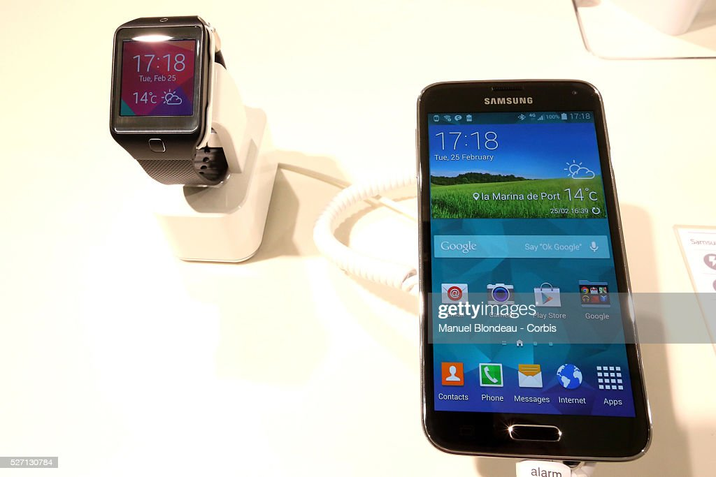 A Galaxy Gear 2 smartwatch sits beside a Galaxy S5 smartphone at the Samsung Electronics Co pavilion during the Mobile World Congress at the Fira...
