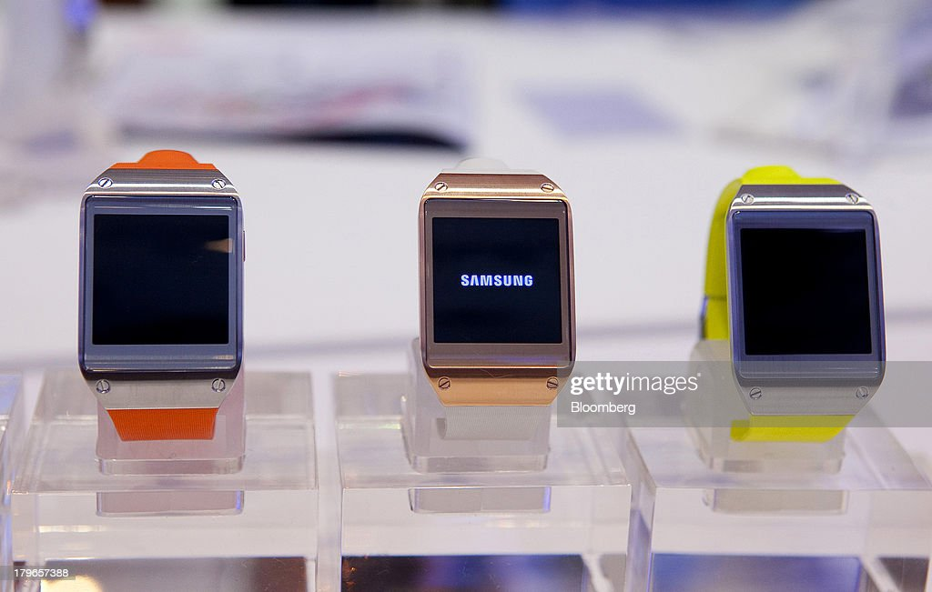 Galaxy Gear smart watches, manufactured by Samsung Electronics Co., sit on display at the IFA consumer electronics show in Berlin, Germany, on Friday, Sept. 6, 2013. Global smartphone revenue will rise 22 percent in 2013, or nearly half the pace of an expected 41 percent gain in shipments, amid falling prices, according to UBS. Photographer: Krisztian Bocsi/Bloomberg via Getty Images