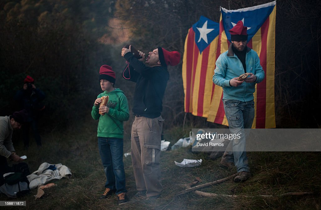 A 'Galejador' drinks wine from a wineskin next to two Catalonian pro-independence flags during 'La Festa del Pi' (The Festival of the Pine) in the village of Centelles on December 30, 2012 in Barcelona, Spain. Early in the morning men and women born in Centelles, who are named 'Galejadors' wear their traditional costume with the Catalan red hat known as 'Barretina' and carry their shooting muskets as they walk into the forest to chop down a pine tree, load it on an ox cart and take it to the church in the village. There the pine tree is decorated with five bouquets of apples and wafers and hung inside a church until January 6. The tradition has been documented since 1751 and it is believed its origins are related to the trees and the pagan worship of fertilization related the winter solstice.