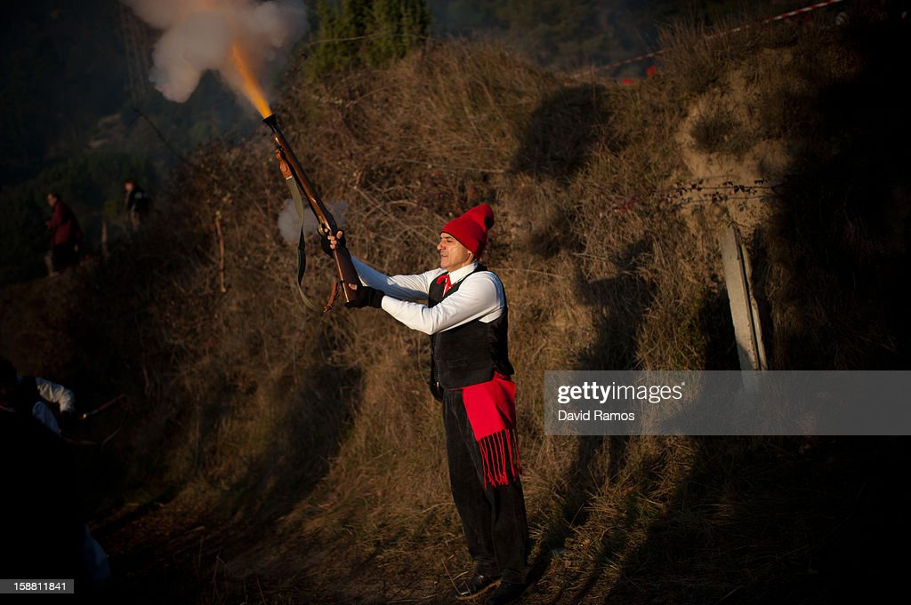 A 'Galejador' fires his musket during 'La Festa del Pi' (The Festival of the Pine) in the village of Centelles on December 30, 2012 in Barcelona, Spain. Early in the morning men and women born in Centelles, who are named 'Galejadors' wear their traditional costume with the Catalan red hat known as 'Barretina' and carry their shooting muskets as they walk into the forest to chop down a pine tree, load it on an ox cart and take it to the church in the village. There the pine tree is decorated with five bouquets of apples and wafers and hung inside a church until January 6. The tradition has been documented since 1751 and it is believed its origins are related to the trees and the pagan worship of fertilization related the winter solstice.