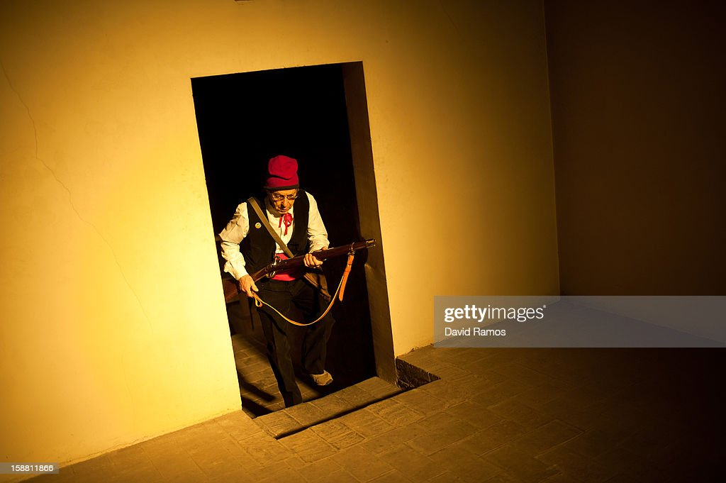 A 'Galejador'gets in the church during 'La Festa del Pi' (The Festival of the Pine) in the village of Centelles on December 30, 2012 in Barcelona, Spain. Early in the morning men and women born in Centelles, who are named 'Galejadors' wear their traditional costume with the Catalan red hat known as 'Barretina' and carry their shooting muskets as they walk into the forest to chop down a pine tree, load it on an ox cart and take it to the church in the village. There the pine tree is decorated with five bouquets of apples and wafers and hung inside a church until January 6. The tradition has been documented since 1751 and it is believed its origins are related to the trees and the pagan worship of fertilization related the winter solstice.