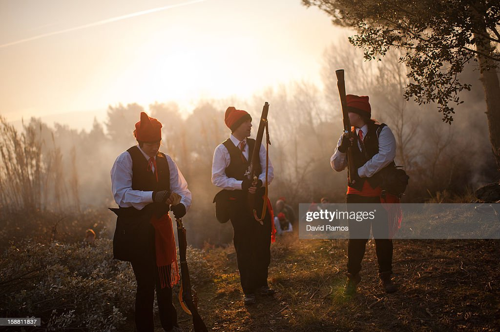 'Galejadors' carry their muskets during 'La Festa del Pi' (The Festival of the Pine) in the village of Centelles on December 30, 2012 in Barcelona, Spain. Early in the morning men and women born in Centelles, who are named 'Galejadors' wear their traditional costume with the Catalan red hat known as 'Barretina' and carry their shooting muskets as they walk into the forest to chop down a pine tree, load it on an ox cart and take it to the church in the village. There the pine tree is decorated with five bouquets of apples and wafers and hung inside a church until January 6. The tradition has been documented since 1751 and it is believed its origins are related to the trees and the pagan worship of fertilization related the winter solstice.