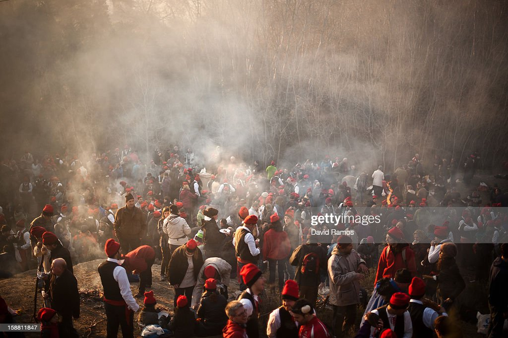 'Galejadors' gather in the forest as they have breakfast during 'La Festa del Pi' (The Festival of the Pine) in the village of Centelles on December 30, 2012 in Barcelona, Spain. Early in the morning men and women born in Centelles, who are named 'Galejadors' wear their traditional costume with the Catalan red hat known as 'Barretina' and carry their shooting muskets as they walk into the forest to chop down a pine tree, load it on an ox cart and take it to the church in the village. There the pine tree is decorated with five bouquets of apples and wafers and hung inside a church until January 6. The tradition has been documented since 1751 and it is believed its origins are related to the trees and the pagan worship of fertilization related the winter solstice.