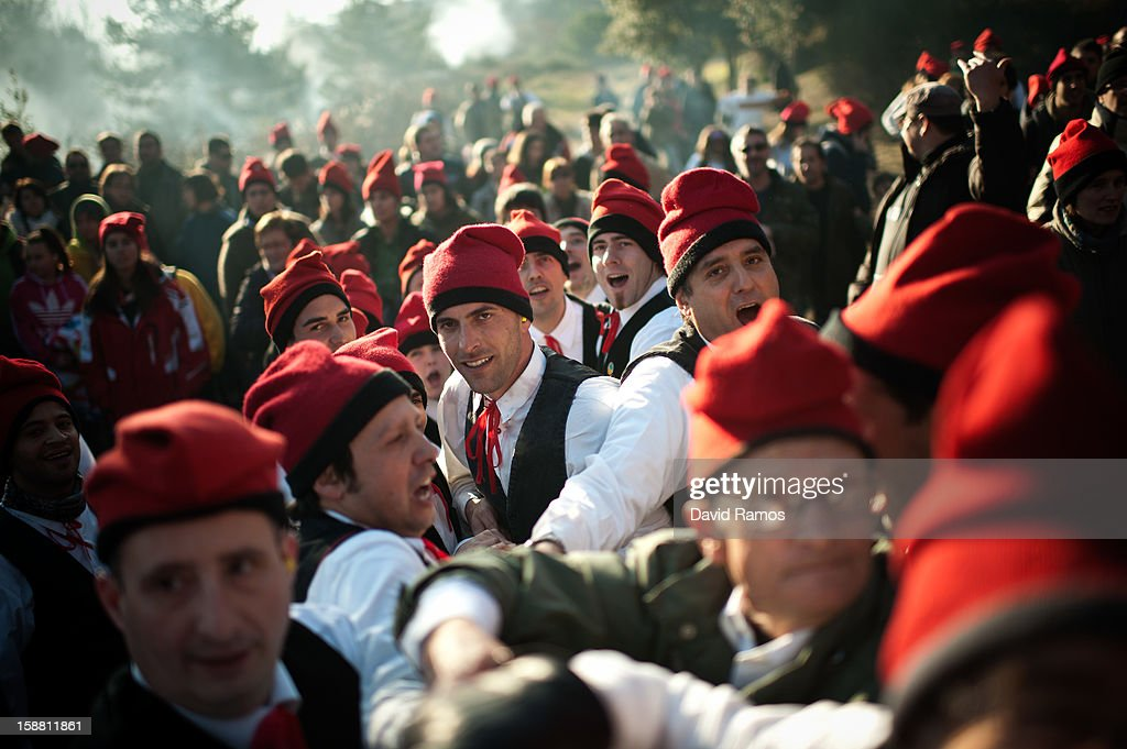 'Galejadors' pull a rope tied to the selected pine tree as it is felled during 'La Festa del Pi' (The Festival of the Pine) in the village of Centelles on December 30, 2012 in Barcelona, Spain. Early in the morning men and women born in Centelles, who are named 'Galejadors' wear their traditional costume with the Catalan red hat known as 'Barretina' and carry their shooting muskets as they walk into the forest to chop down a pine tree, load it on an ox cart and take it to the church in the village. There the pine tree is decorated with five bouquets of apples and wafers and hung inside a church until January 6. The tradition has been documented since 1751 and it is believed its origins are related to the trees and the pagan worship of fertilization related the winter solstice.